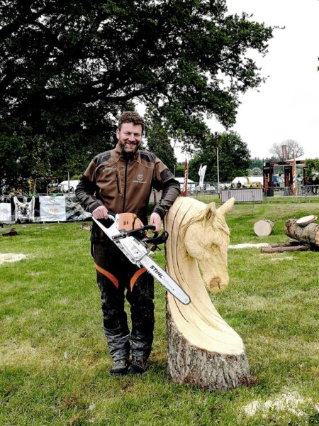 simon o'rourke stands next to a horse carving holding a chainsaw at the arb show 2019, one of his top chainsaw carving events