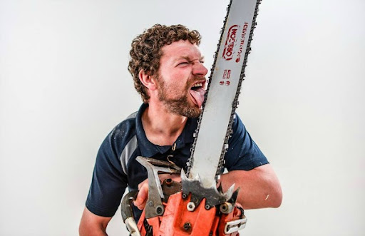 chainsaw artist simon o'rourke holds a large chainsaw and licks the blade