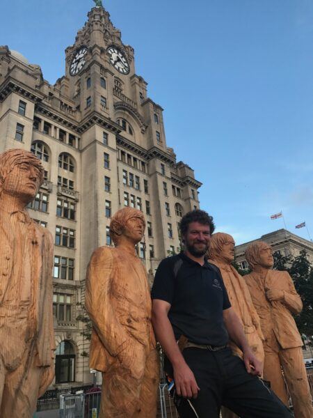 simon o'rourke with his chainsaw carving sculptures of the beatles on the liverpool pierhead