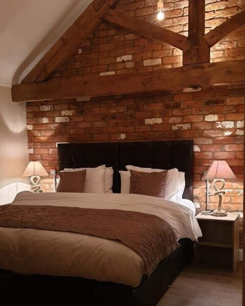 Double bed with brick wall beind and wooden beams. Bedroom at Lower Farm Holiday Cottages