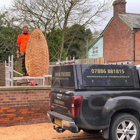 chainsaw artist simon o'rourke stands next to a 6' tree stump being carved into a giant pinecone sculpture