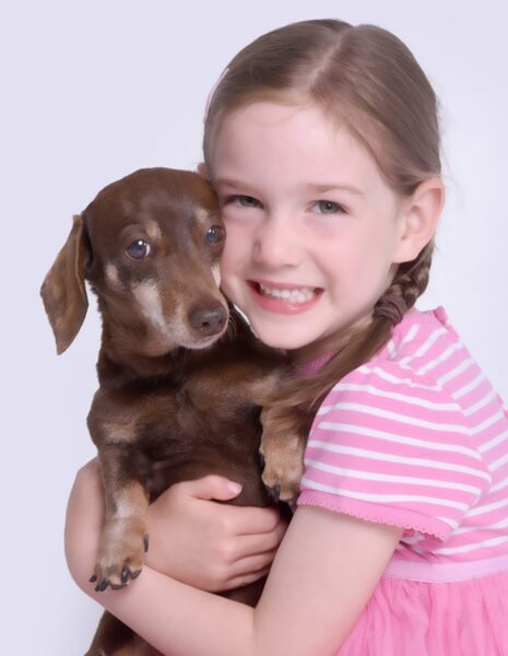 A young girl holding her pet dachshund Fudge. He is the cntral character of the Lower Farm Sculpture Trail
